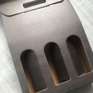 Coffret cartonné marron foncé pour offrir 3 bouteilles (vin, bière) de dimensions : 27x37x9, avec une poignée.