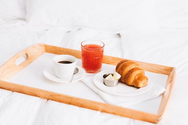 tasse de café, jus de fruits, céréales, pain, confiture sur un plateau petit déjeuner